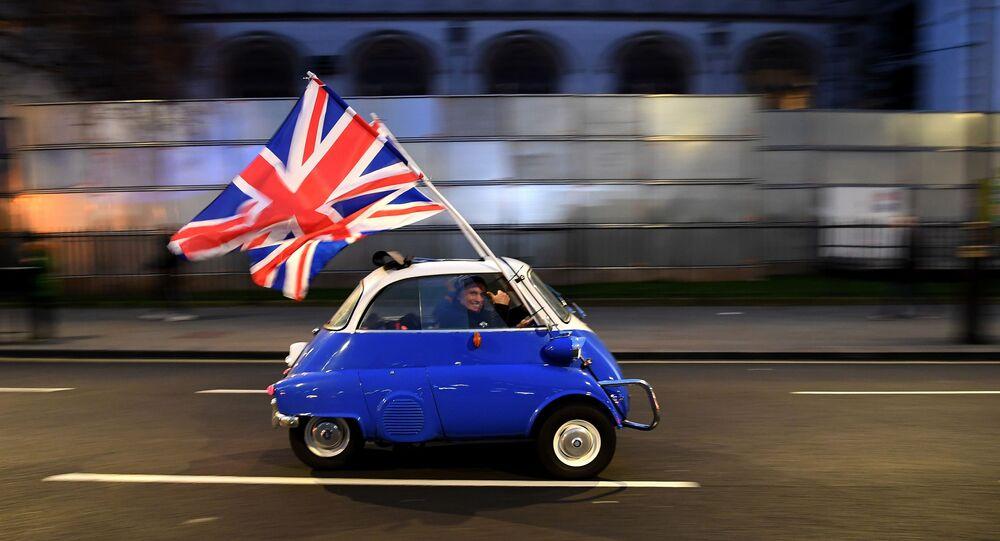 Mężczyzna z flagami Wielkiej Brytanii w centrum Londynu w dzień oficjalnego wyjścia kraju z UE