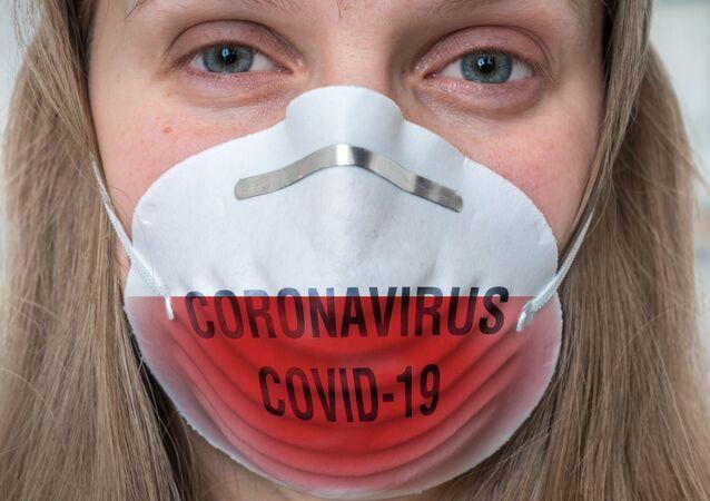 """Kobieta w masce medycznej w kolorach polskiej flagi z napisem """"koronawirus COVID-19"""""""