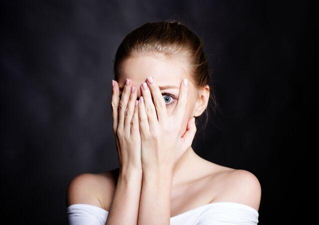 Dziewczyna zakrywa twarz rękoma