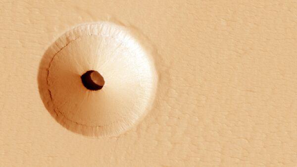 Zagłębienie o średnicy około 35 metrów, otoczone niemal idealnie okrągłym kraterem, odkryto na zachodnim zboczu  Pavonis Mons.  - Sputnik Polska