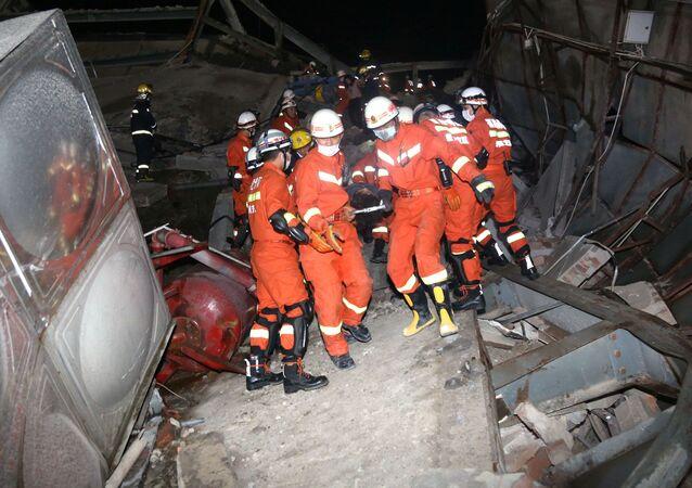 Ratownicy na miejscu zawalenia się hotelu, Chiny