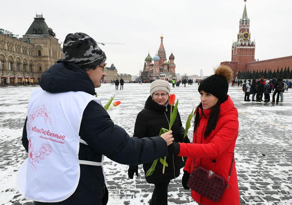 Wolontariusz daje kwiaty kobietom na Placu Czerwonym