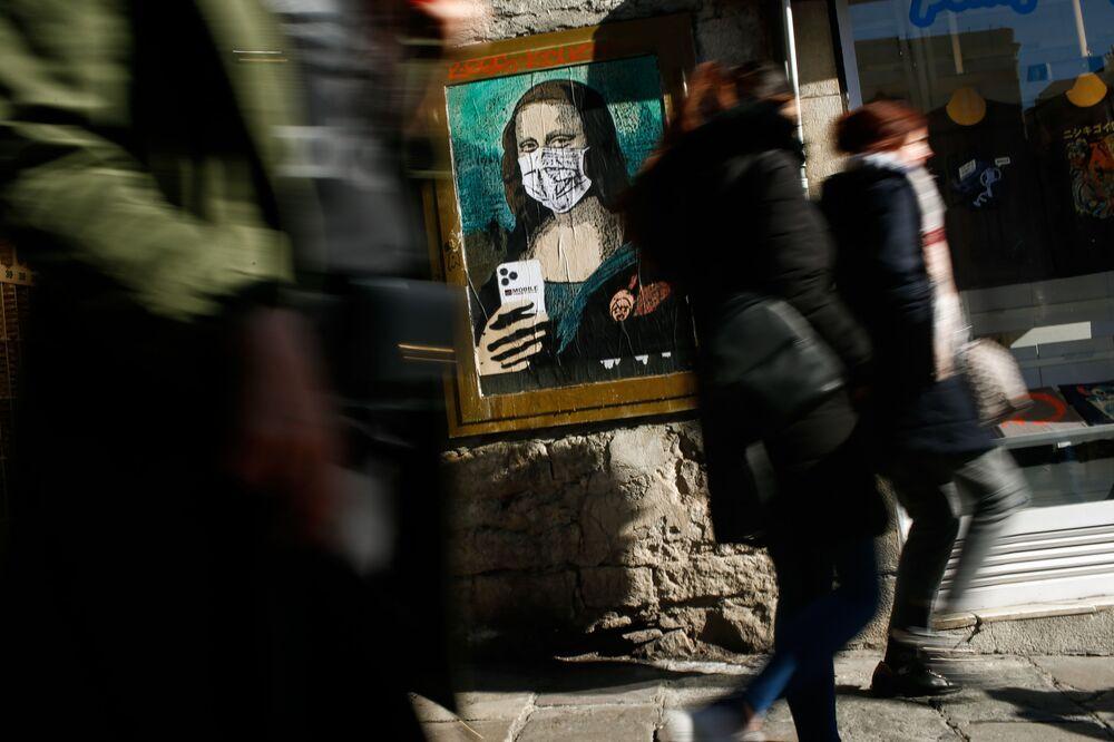 """Obraz """"Mona Lisa"""" Leonarda da Vinci w masce medycznej na ulicy w Barcelonie"""
