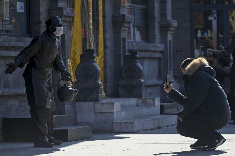 Mężczyzna fotografuje posąg w masce medycznej w Pekinie