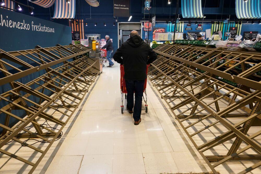 Mężczyzna przed pustymi półkami w supermarkecie, Hiszpania.