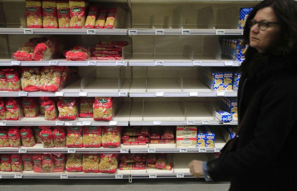 Kobieta przed pustymi pułkami w supermarkecie w Paryżu.