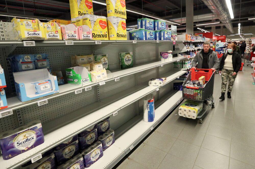 Kliencie przed pustymi półkami w supermarkecie w Berlinie.