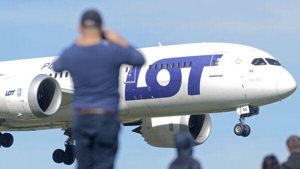 Mężczyzna fotografuje samolot LOT - Sputnik Polska