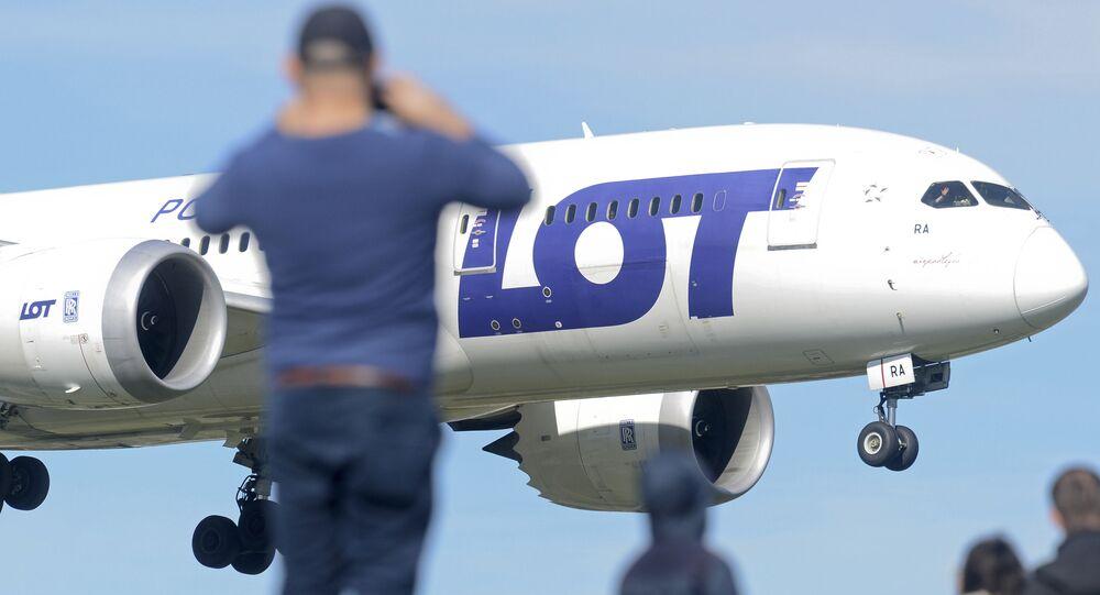 Mężczyzna fotografuje samolot LOT