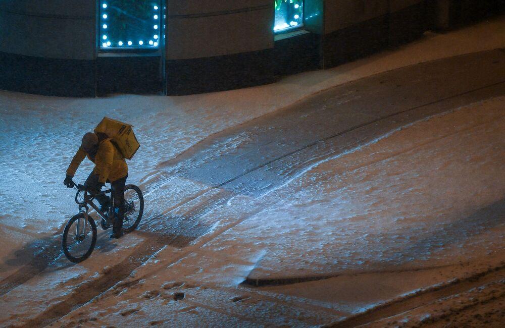 """Kurier """"Yandex.Eat"""" jeździe na rowerze podczas opadów śniegu w Moskwie."""