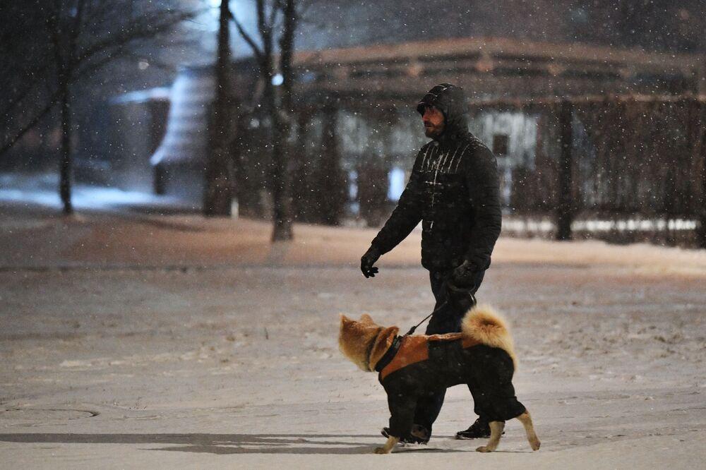 Mężczyzna z psem podczas opadów śniegu w Moskwie.