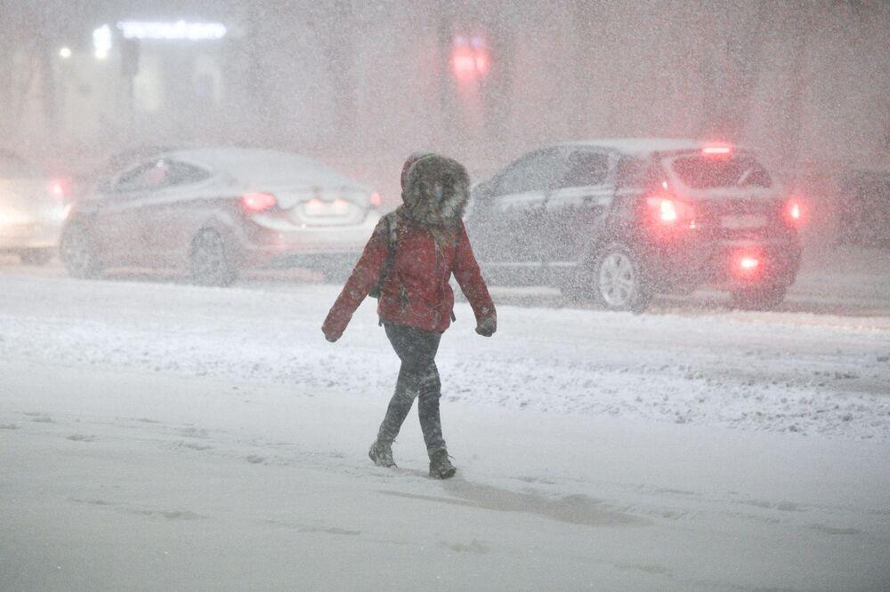 Kobieta w masce podczas opadów śniegu w Podolsku.