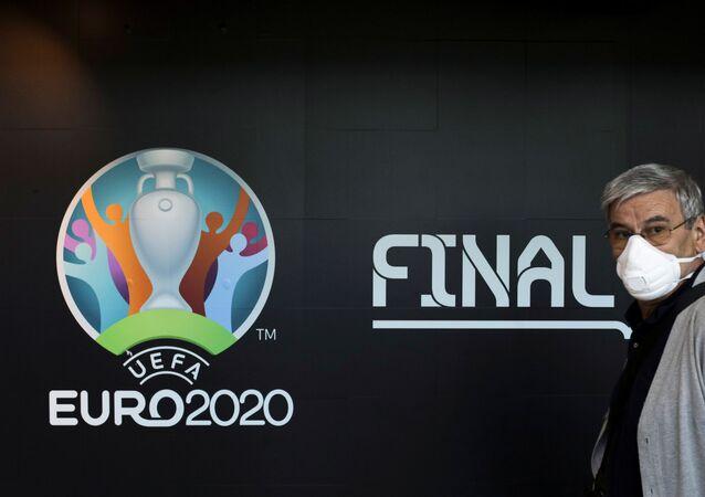 Turysta w masce medycznej przy stoisku z logo Mistrzostw Europy w piłce nożnej 2020 na lotnisku w Bukareszcie.