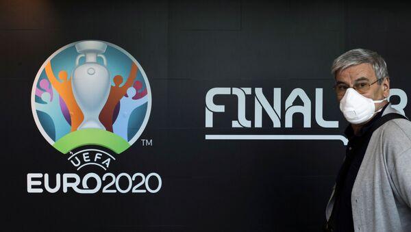 Turysta w masce medycznej przy stoisku z logo Mistrzostw Europy w piłce nożnej 2020 na lotnisku w Bukareszcie - Sputnik Polska