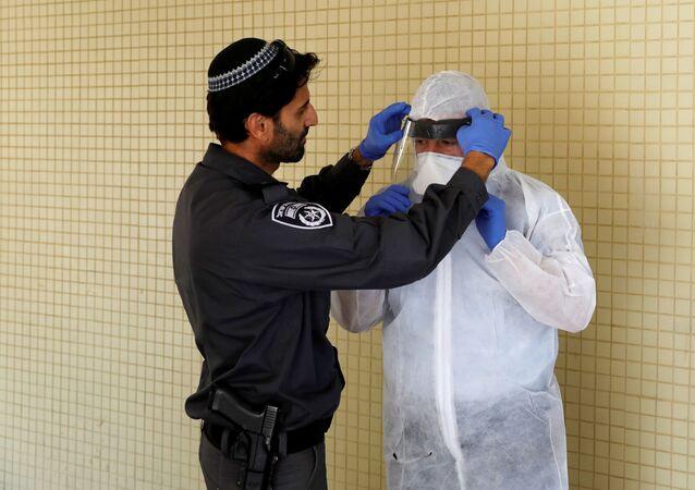 Izraelski policjant pomaga inspektorowi Ministerstwa Zdrowia nałożyć sprzęt ochronny przed mieszkaniem osoby poddanej kwarantannie