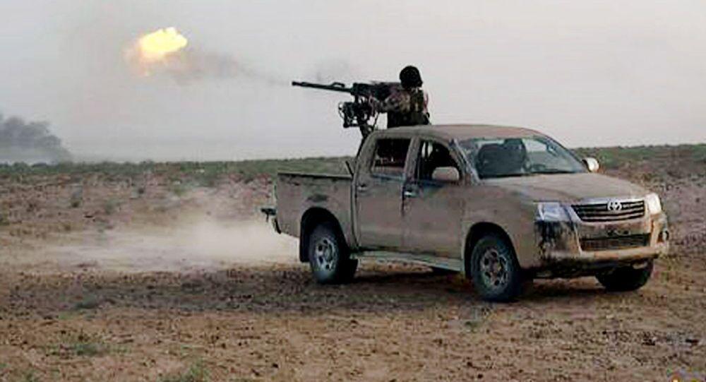 Terrorysta Państwa Islamskiego strzela w kierunku armii rządowej Baszara al-Asada