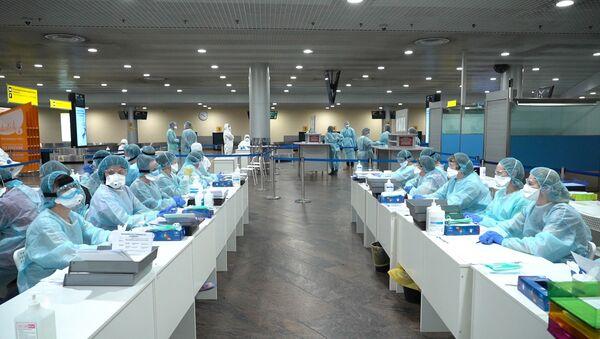 Pracownicy służby medycznej przygotowani do kontroli pasażerów na moskiewskim lotnisku Szeremietiewo  - Sputnik Polska