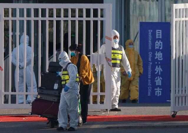 Pracownik w kombinezonie ochronnym na lotnisku w Pekinie