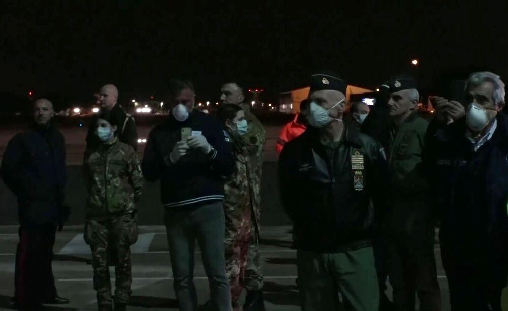 Włoscy żołnierze oczekują przylotu wojskowego samolotu transportowego rosyjskich sił powietrznych Il-76 MD ze sprzętem medycznym przeznaczonym do zwalczania wirusa COVID-19