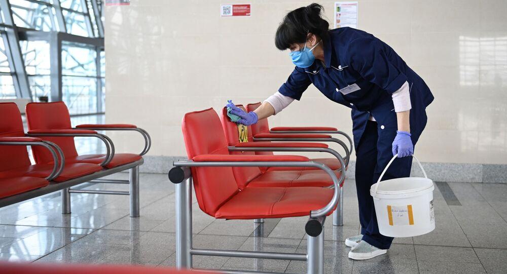 Pracownica firmy sprzątającej w maseczce dezynfekuje powierzchnie na dworcu w Adler