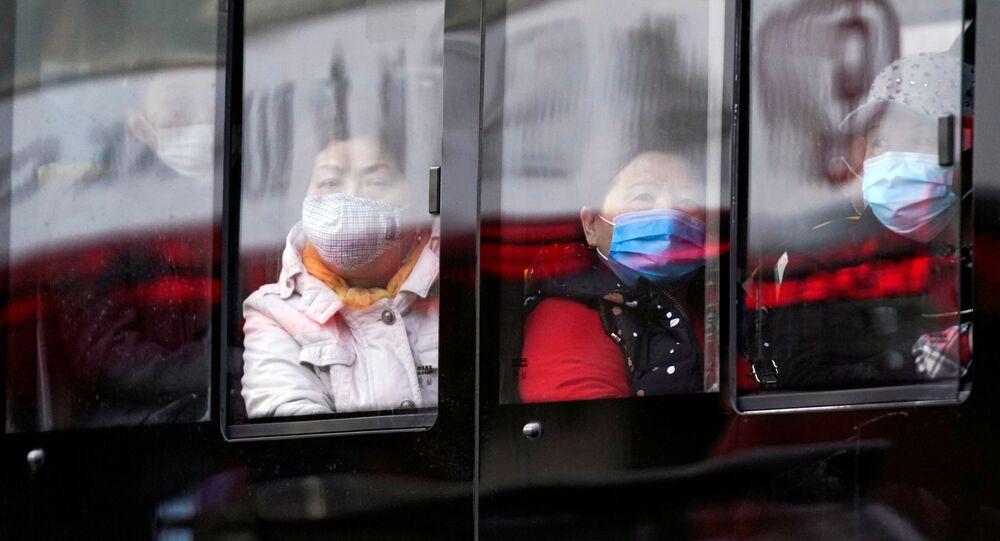 Ludzie w maseczkach jadą autobusem w Szanghaju