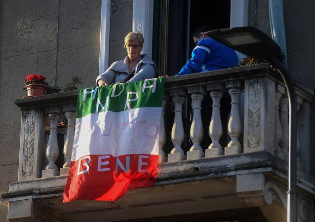 Kobieta na balkonie z flagą Włoch z napisem Wszystko będzie dobrze