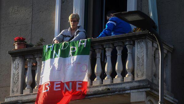 Kobieta na balkonie z flagą Włoch z napisem Wszystko będzie dobrze - Sputnik Polska