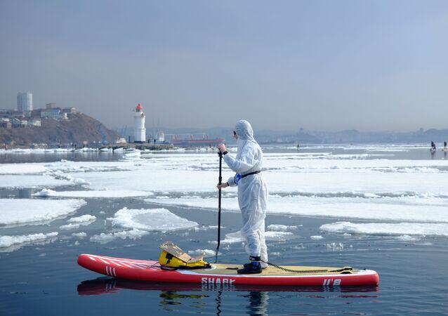 Surfer w kombinezonie ochronnym w zatoce w pobliżu Władywostoku