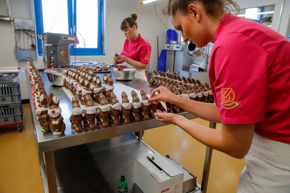 Pracownicy przygotowują czekoladowe króliki wielkanocne w maskach ochronnych w piekarni Baeckerei Bohnenblust w Bernie w Szwajcarii
