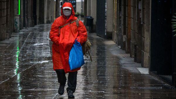 Mężczyzna w masce ochronnej na ulicy Barcelony - Sputnik Polska