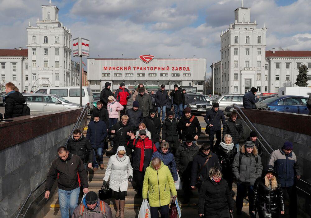 Ludzie kończą swoją zmianę w pracy w Mińskim Zakładzie Ciągników i udają się do swoich domów