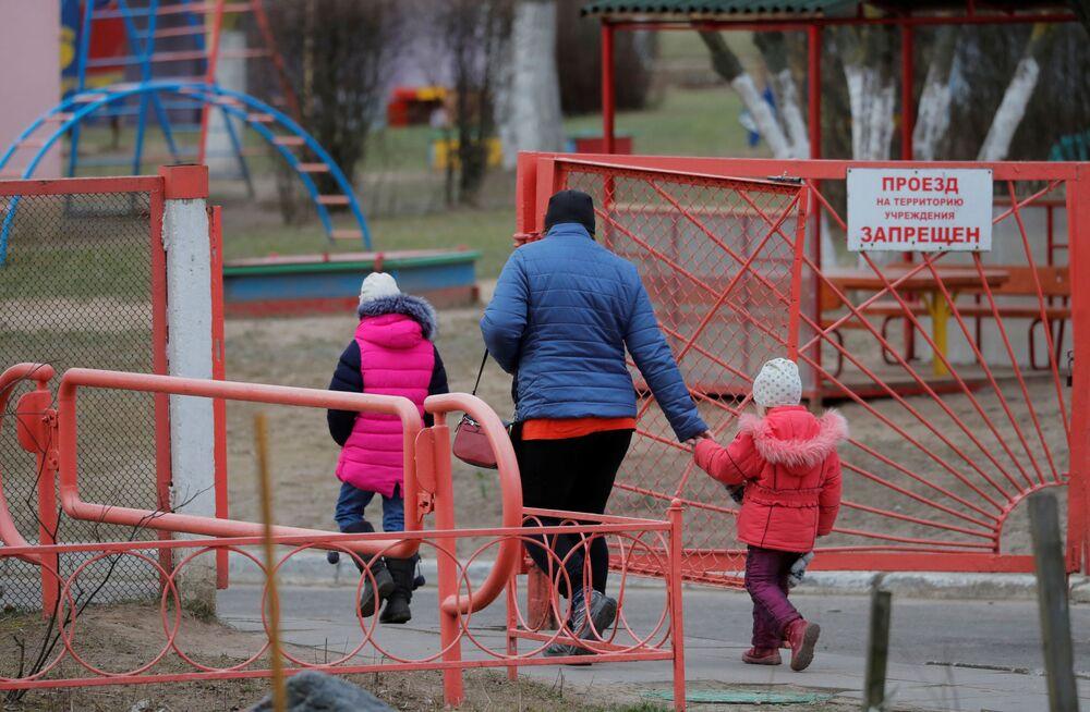Kobieta spaceruje z dziećmi w Mińsku