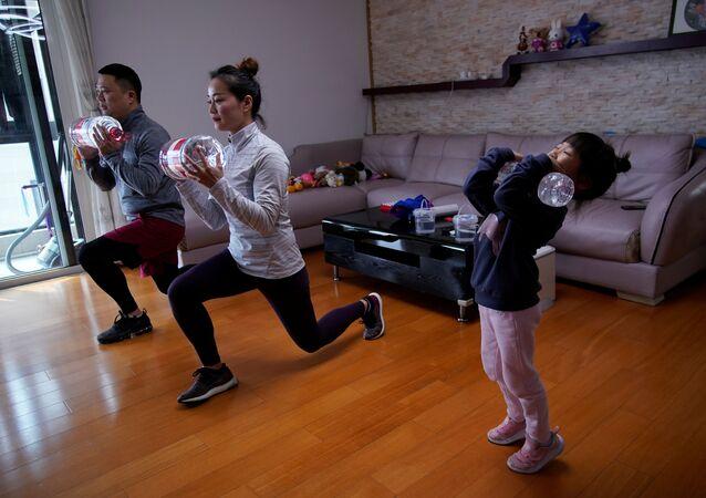 Chińska rodzina ćwiczy w domu, używając butelek z wodą