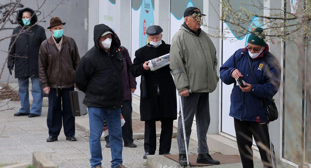 Starsi ludzie w maskach medycznych pod apteką w Sofii, Bułgaria