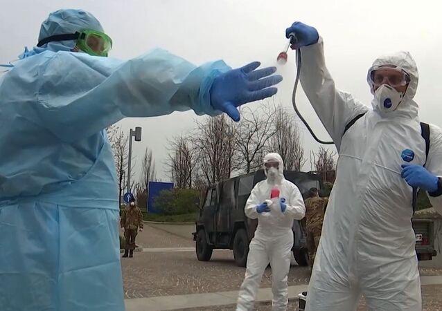 Rosyjscy eksperci wojskowi dezynfekują kombinezony po wizycie w szpitalu dla osób starszych w Bergamo, we Włoszech, w celu walki z zakażeniem koronawirusem COVID-19