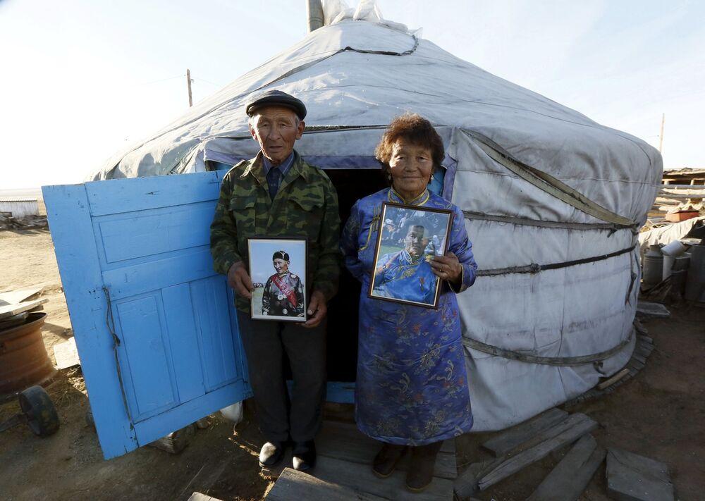 Mieszkańcy Tuwy przy wejściu do Jurty trymają zdjęcia rodaków