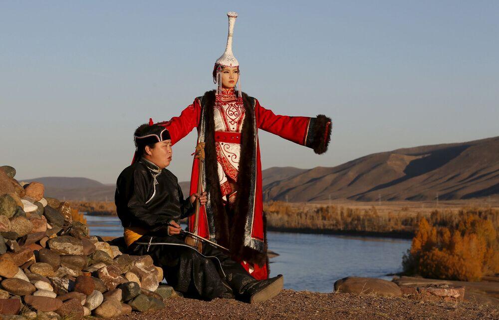 Mistrz śpiewu alikwotowego z dziewczyną ubrani na tadycyjno są nad brzegiem rzeki Jenisiej w Tuwie