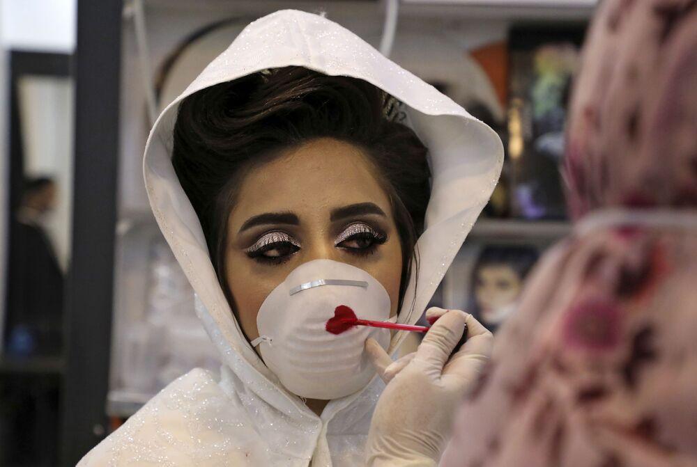 Palestyńska panna młoda maluje maskę na ceremonii ślubnej