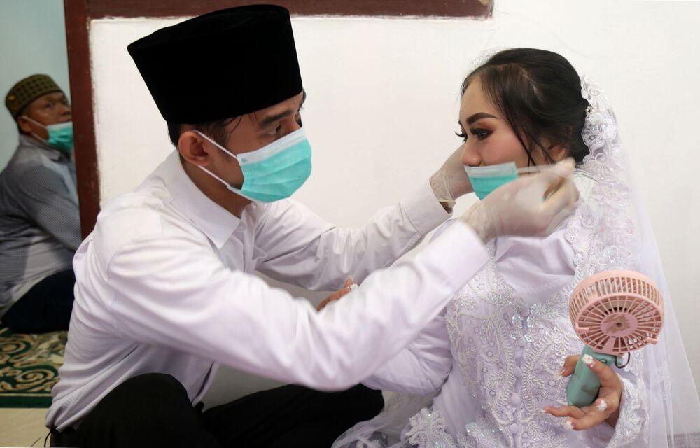 Panna młoda i pan młody w maskach medycznych przed ceremonią ślubną w Dżakarcie