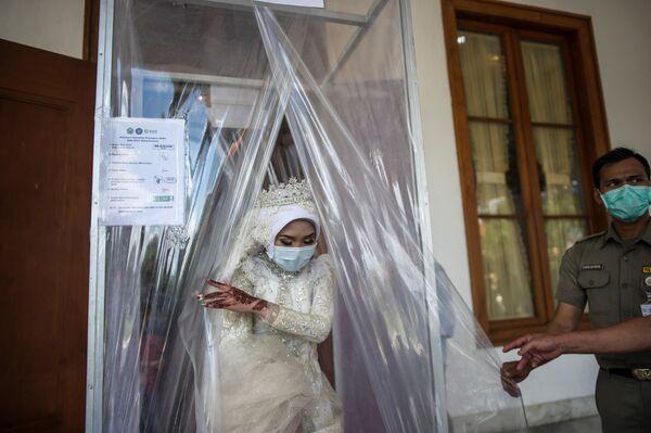 Indonezyjska panna młoda po dezynfekcji podczas ceremonii ślubnej w mieście Surabaja - Sputnik Polska