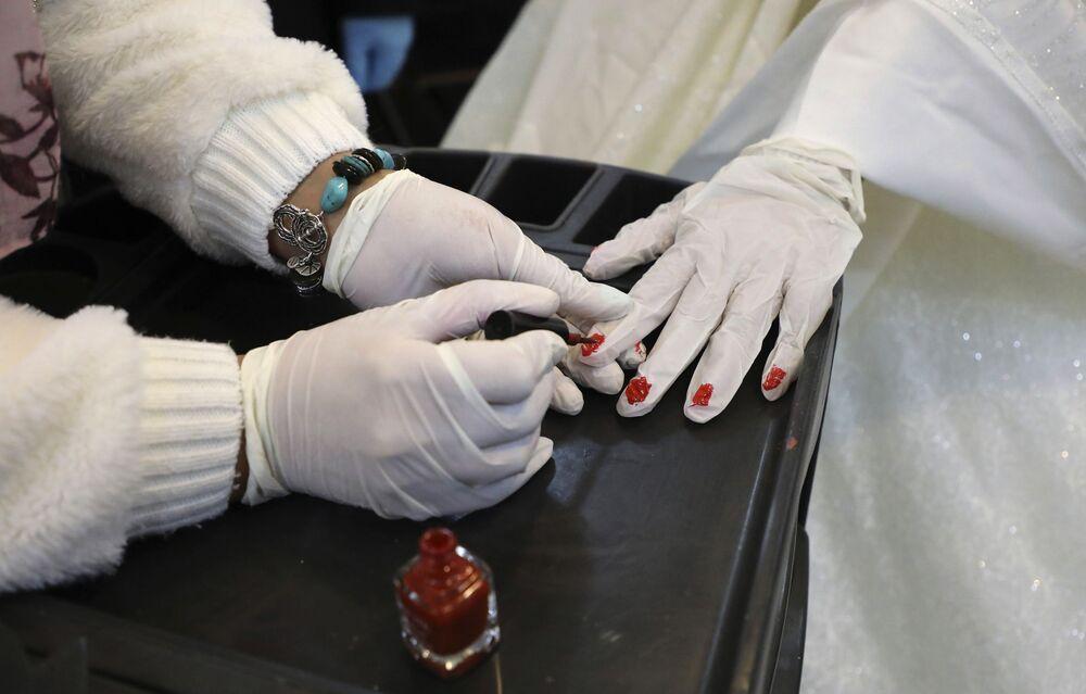 Palestyńska panna młoda maluje paznokcie na rękawiczkach przed ceremonią ślubną w wiosce Dora w pobliżu Hebronu
