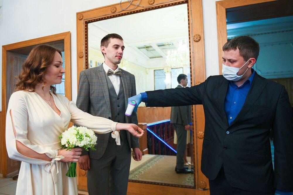 Pracownik urzędu stanu cywilnego sprawdza parze temperaturę przed ślubem w Moskwie