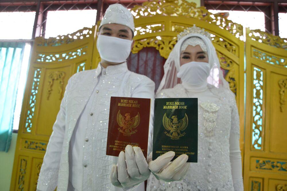 Nowożeńcy z dokumentami potwierdzającymi zawarcie związku małżeńskiego w Dżakarcie