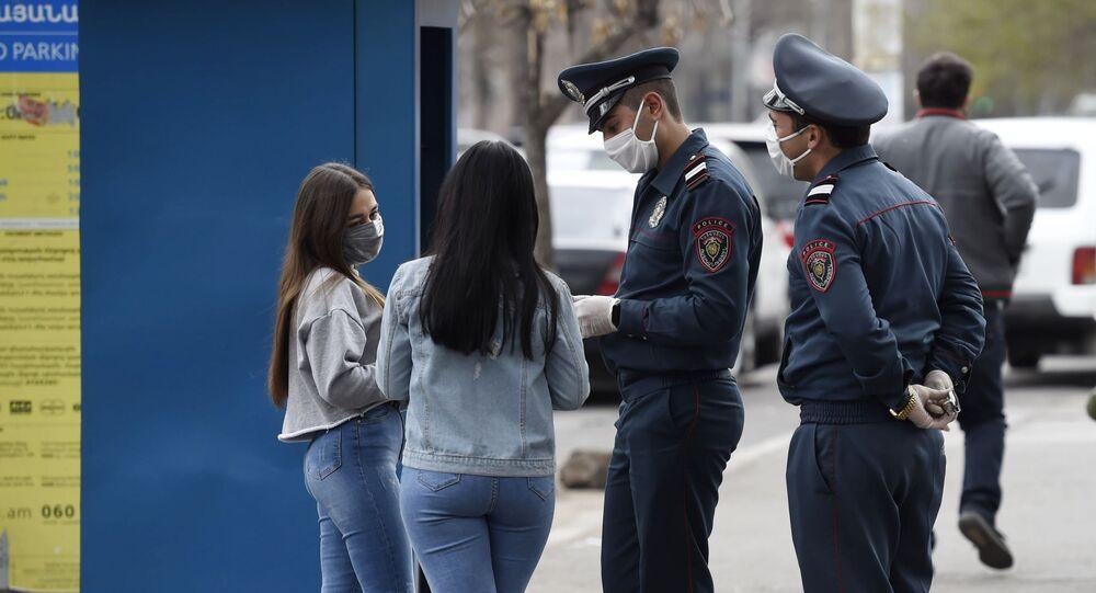 Funkcjonariusze policji i mieszkańcy w maseczkach ochronnych na jednej z ulic Erywania