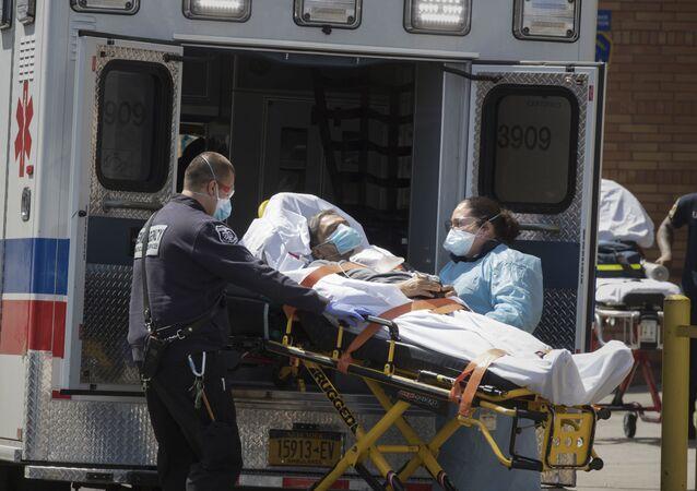 Personel medyczny wyprowadza pacjenta na noszach z karetki w Brooklynie w Nowym Jorku
