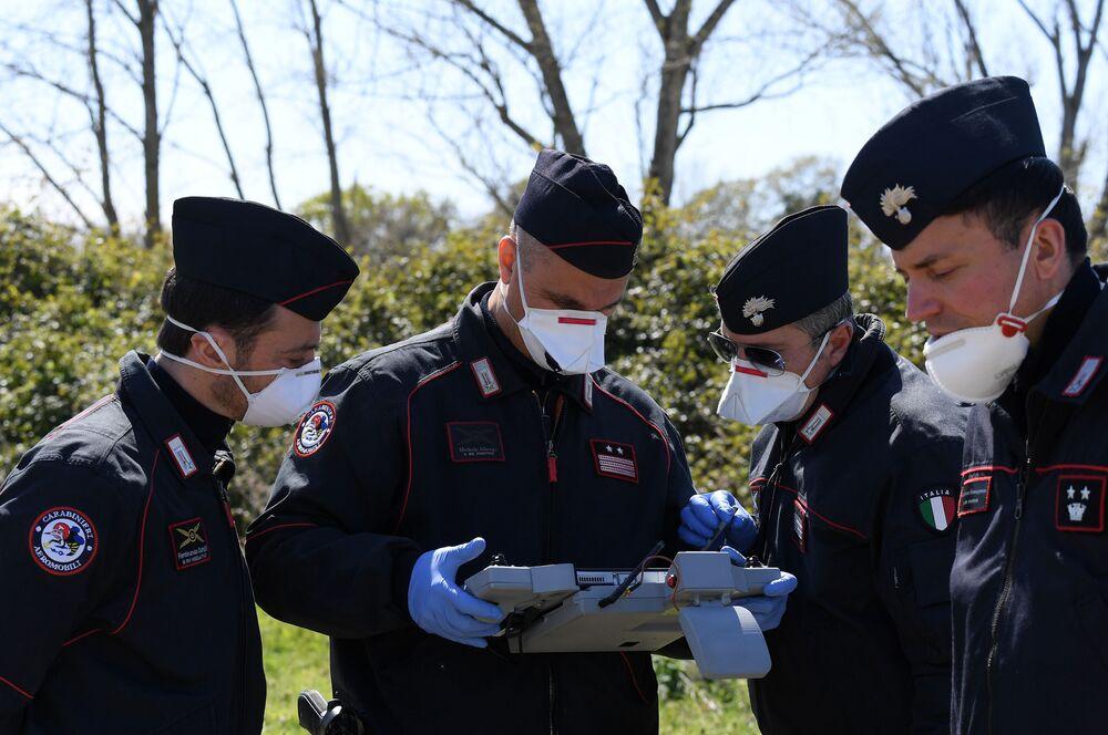 Carabinieri z panelem sterowania dronami w celu sprawdzenia, czy ludność przestrzega środków wprowadzonych w związku z koronawirusem w Rzymie we Włoszech.