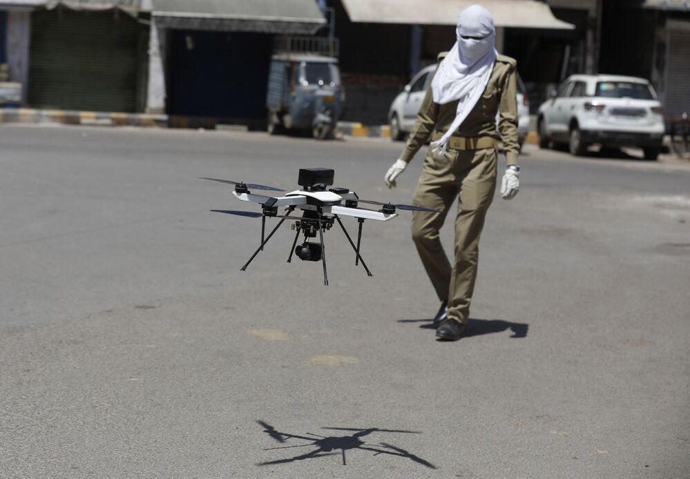 Indyjski policjant obserwuje drona, który sprawdza przestrzeganie kwarantanny.