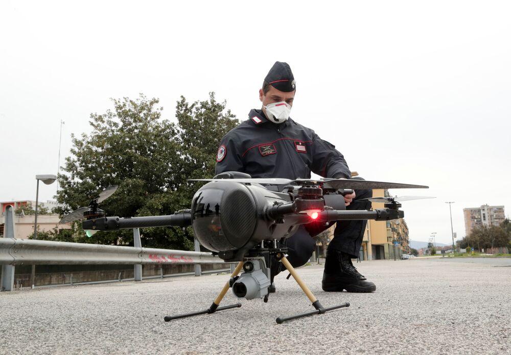 Włoski carabinieri obsługuje drona w celu sprawdzenia, czy ludność wdraża środki wprowadzone przez rząd w związku z koronawirusem w Neapolu we Włoszech.