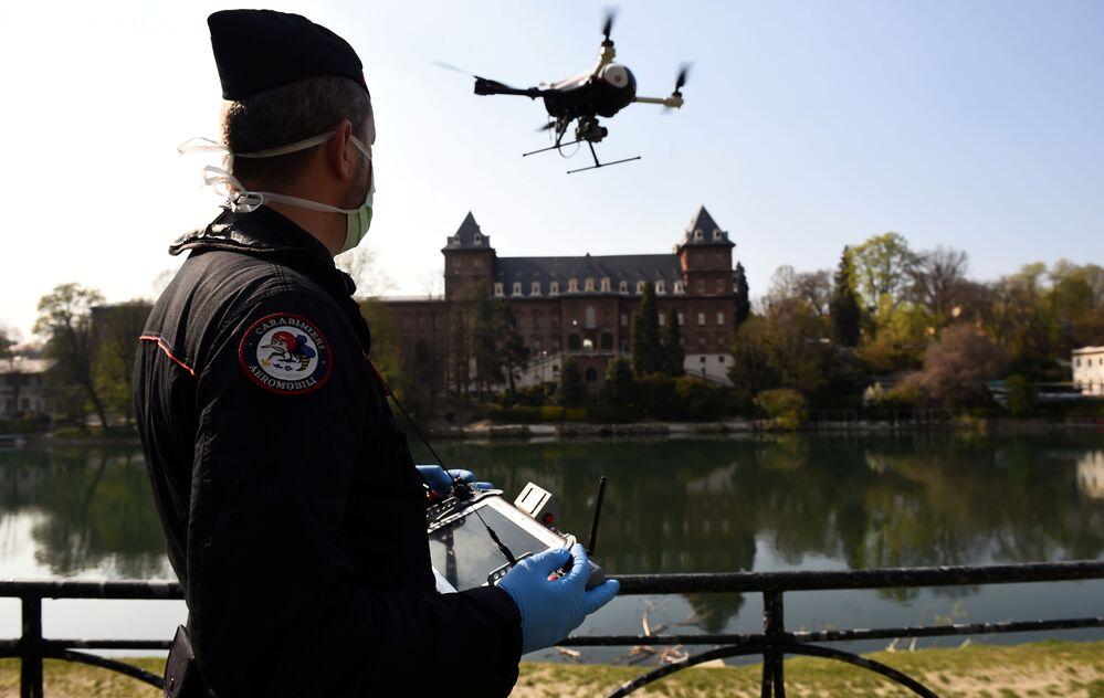 Włoski carabinieri obsługuje drona w celu sprawdzenia, czy ludność wdraża środki wprowadzone przez rząd w związku z koronawirusem w Turynie we Włoszech.