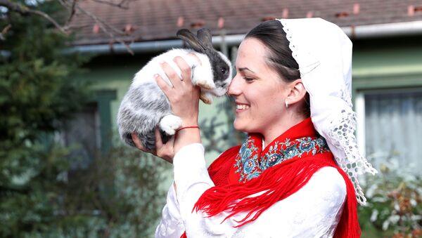 Kobieta w stroju ludowym z królikiem podczas uroczystości wielkanocnych na Węgrzech - Sputnik Polska